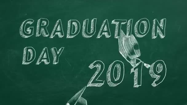 Hand drawing text Graduation day. 2019. and graduation caps  on green chalkboard.