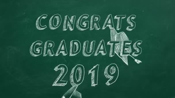 Hand drawing text Congrats graduates. 2019. and graduation caps  on green chalkboard.