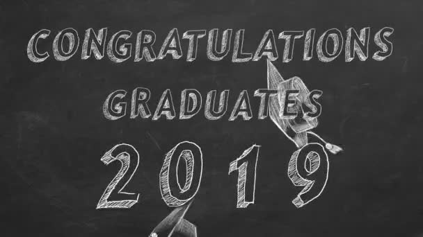Hand drawing text Congratulations graduates.  2019. and graduation caps   on blackboard.