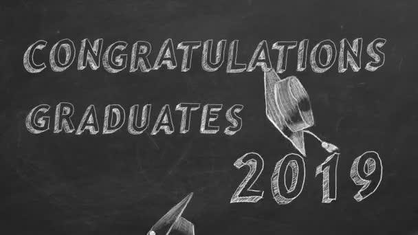 Hand drawing text Congratulations graduates.  2019. and graduation caps on blackboard.