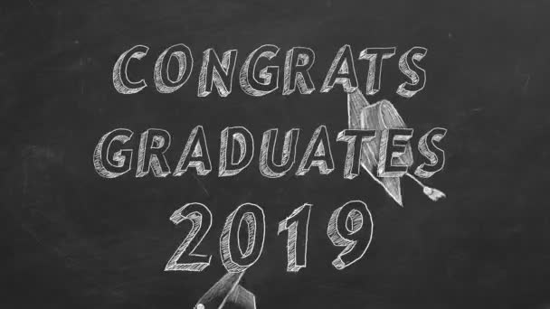 Hand drawing text Congrats graduates. 2019. and graduation caps on blackboard.