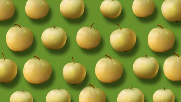 Colorful fruit pattern of fresh yellow apples on green background. 4k video.