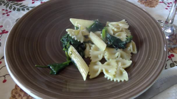 Leftover pasta recipe made of farfalle, penne rigate and spinach, dressed with parmesan cheese and hot chili pepper.
