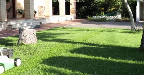 Muž sekající trávník před domem sekačkou na trávu.
