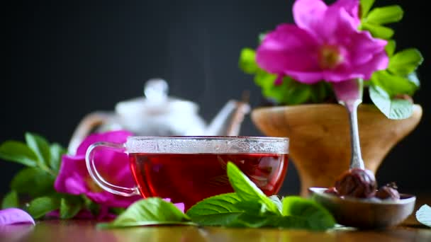 tea made from rose hips with mint on a wooden table with flowers