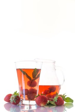 Sweet compote of ripe red strawberries in a glass decanter on a white background