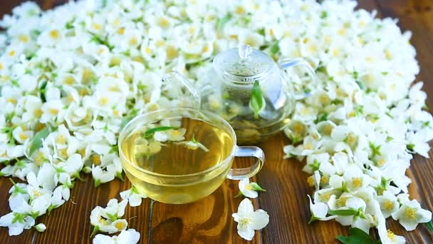 Tea with jasmine flowers in a glass teapot on a table