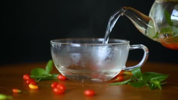 horký čaj od zralé červené goji bobule ve skleněné konvici na dřevěný stůl