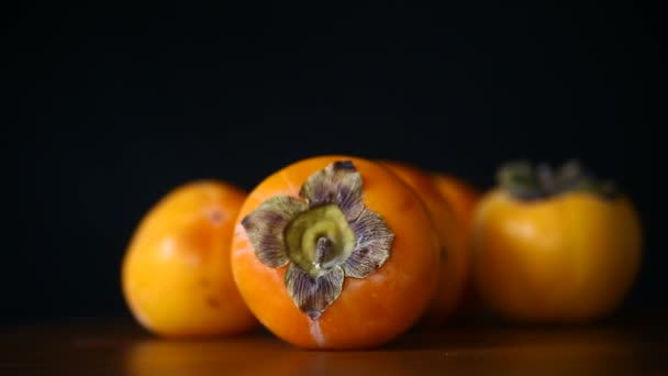 ripe exotic orange sweet persimmon on black