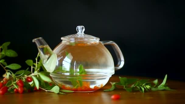 horký čaj od zralé červené goji bobule ve skleněné konvici