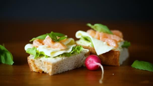 sajtos szendvics, salátalevél és vörös hal a fából készült