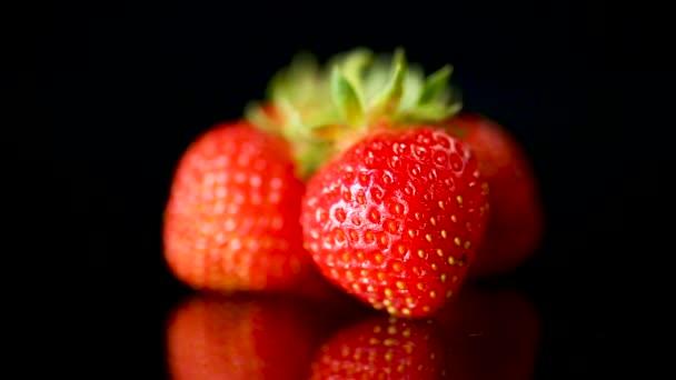 Zralé červené jahody na černém pozadí