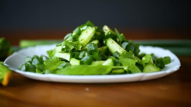 čerstvý salát z okurek a zelených v talíři na dřevěném