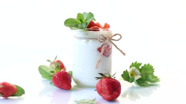 sladký domácí jogurt se zralými čerstvými jahodami ve sklenici
