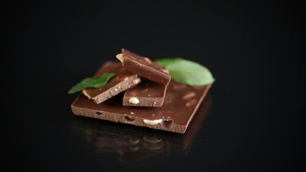 sladká tmavá čokoláda s ořechy na černém pozadí