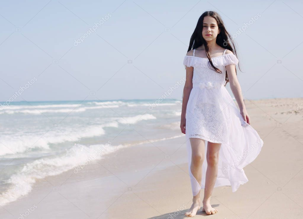 Portrait of aborable 12 years old girl walking alone on the beach in summer day