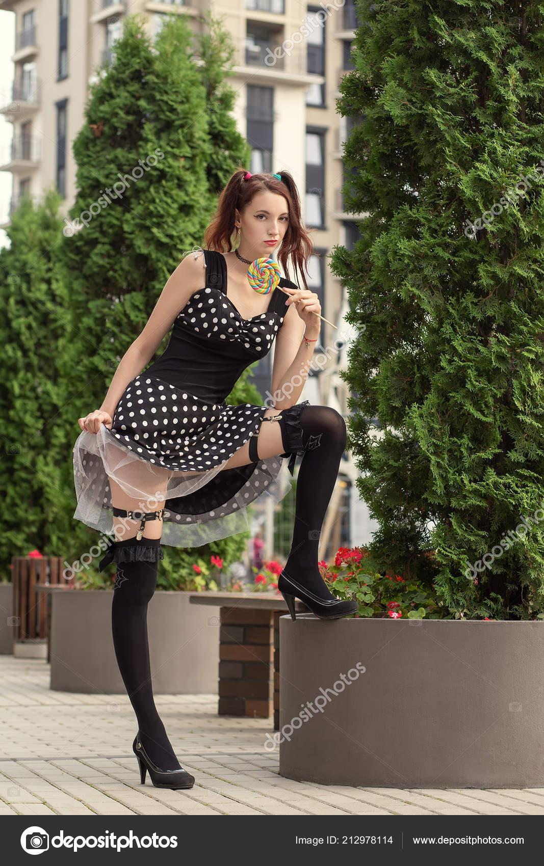 Mujer Joven Atractiva Con Piruleta Vestido Negro Muestra Sus