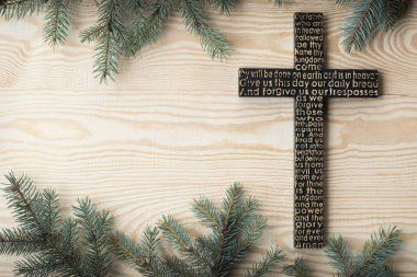 Black wooden cross with the Lords prayer on the shabby wooden plank with fir tree branches background