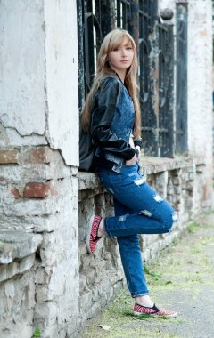 Beautiful sexy young blond woman in torn jeans posing on the streets of the old town