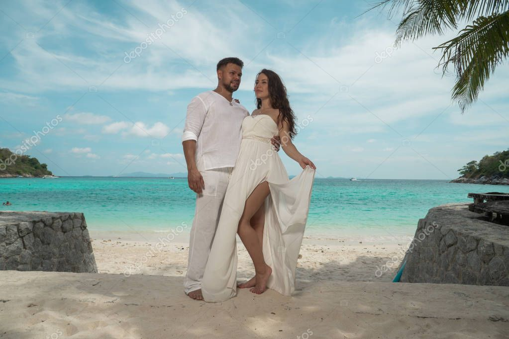 Attractive young couple on the tropical island. Beautiful woman and man wearing white clothes embracing each other and enjoying trpoical holidays vacation getaway