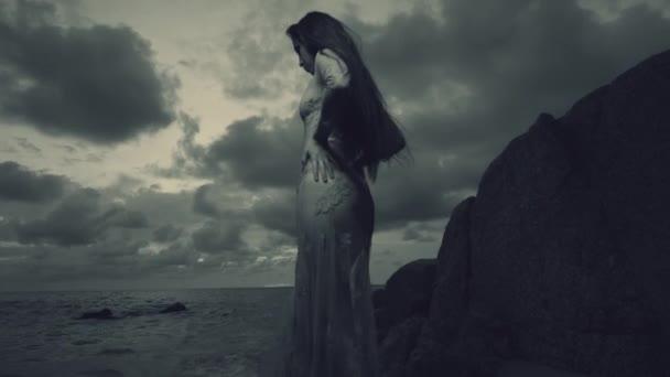 Tajemná krása na pláži při západu slunce / krásná tajemná žena v dlouhých šatech na písečné pláži poblíž skály nad moře a západ slunce oblohou pozadí - černé a bílé video v pomalém pohybu