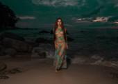 Krásná tajemná žena v dlouhých šatech, stojící na pobřeží moře a západ slunce oblohou pozadí