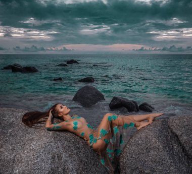 Beautiful mysterious woman in long dress laying down on the rocks over sea and cloudy sunset sky background