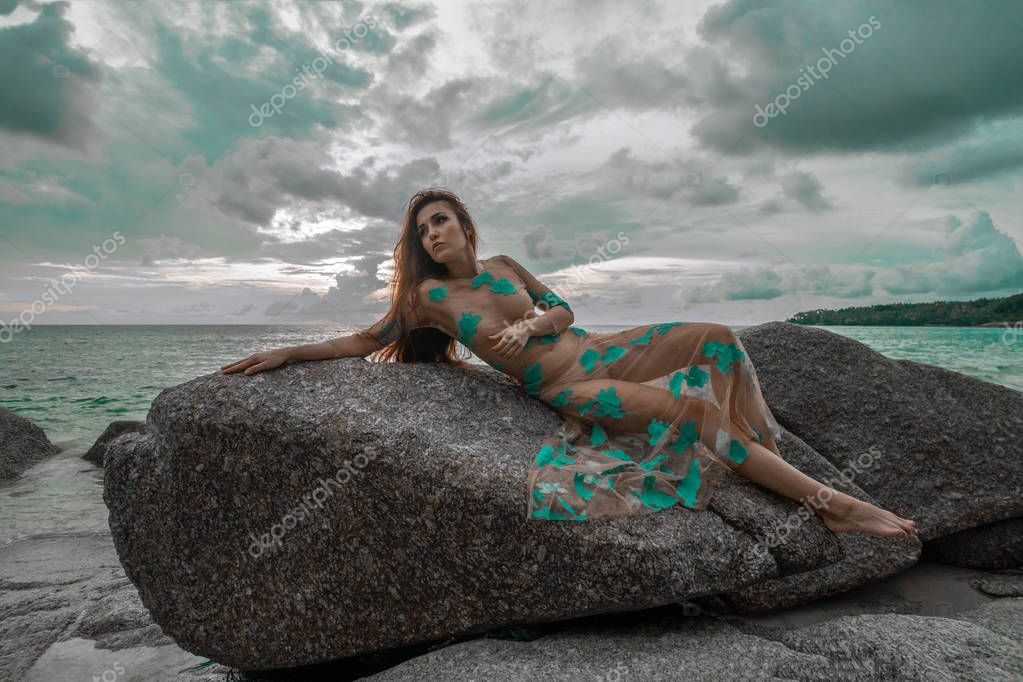 Beautiful mysterious woman in long dress laying down on the rock over sea and cloudy sunset sky background