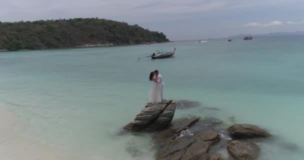 Vonzó a fiatal pár, a trópusi szigeten / légi Nézd vonzó fiatal pár a trópusi szigeten. Gyönyörű nő és férfi, fehér ruhában, ölelni egymást, és élvezi a trópusi ünnepek vacation getaway