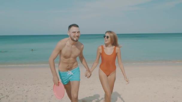 Boldog pár frizbi a frizbi repülő korong játszik a tengerparton napsütéses nyári napon beach/boldog pár