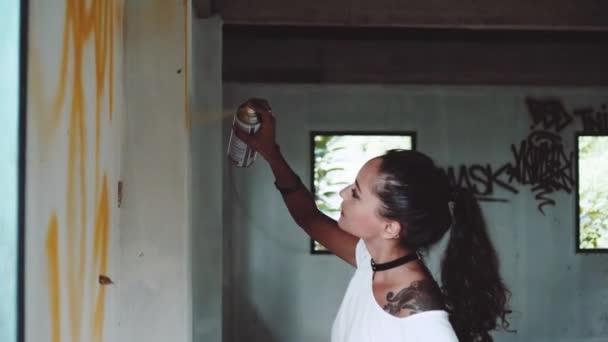 Graffiti umělec dívka/Graffiti umělec dívka malba na zdi opuštěné budovy. Pretty woman s aerosolový rozprašovač postřik s barevné barvy. Koncepce umění městské venku