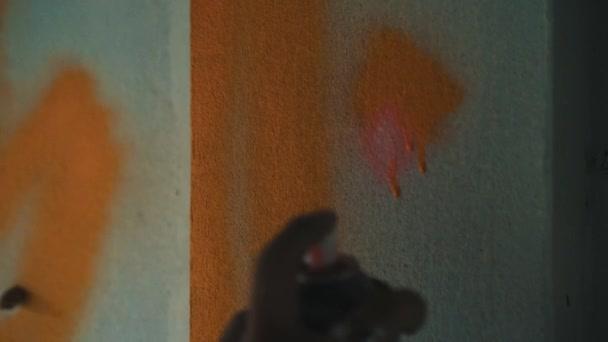 Graffiti umělec dívka/Graffiti umělec dívka malba na zdi opuštěné budovy. Closeup ruka ženy s aerosolový rozprašovač postřik s barevné barvy. Koncepce umění městské venku
