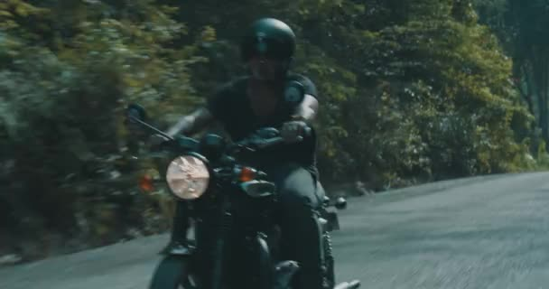 Zdarma motocykl jezdce/boční pohled na super turistické jízdě svůj chopper motorky na silnici tropický ostrov s výhledem na pozadí zelených stromů během letního dne - video v pomalém pohybu