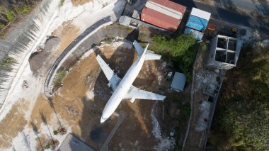 Aerial top drone view of abandoned airplane, old crashed aircraft wreck tourist attraction located in South Kuta, Bali, Indonesia