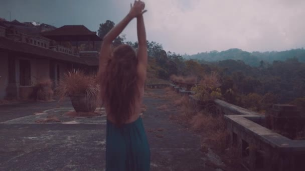 Beautiful woman on the terrace of abandoned hotel / Beautiful woman in dress walking on the terrace of abandoned hotel with amazing mountain view - video in slow motion