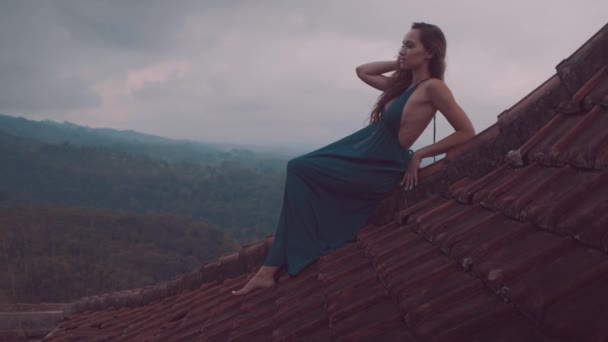 Beautiful woman sitting on the red house rooftop / Beautiful woman in long blue dress sitting on tiled red roof of the house against amazing mountain view and cloudy sky background - video in slow motion