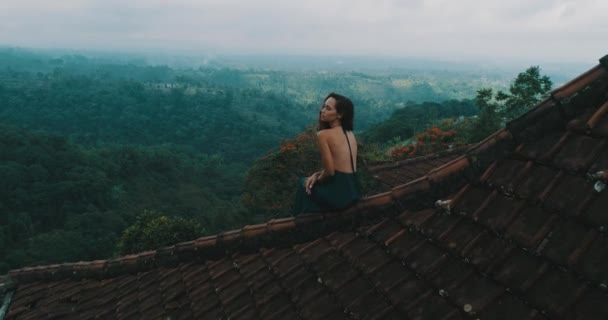 Beautiful woman sitting on the red house rooftop / Aerial drone view of beautiful woman in long blue dress sitting on tiled red roof of the house against amazing mountain view and cloudy sky background - video in slow motion