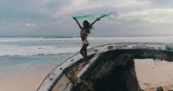 Aerial drone view of beautiful girl with colored smoke standing on the shipwreck at the beach during amazing sunset - video in slow motion