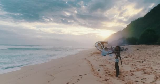 Aerial drone view of beautiful girl playing with colored smoke near the shipwreck at the beach during amazing sunset - video in slow motion