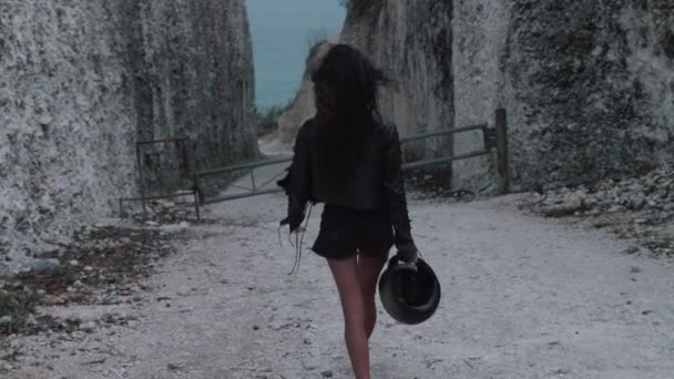Back view of beautiful woman motorcycle rider walking with helmet near amazing limestone cliffs - video in slow motion