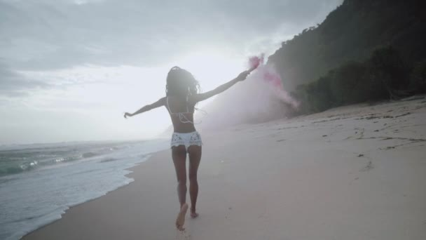Beautiful happy girl running with colored smoke at the sandy beach during amazing sunset - video in slow motion