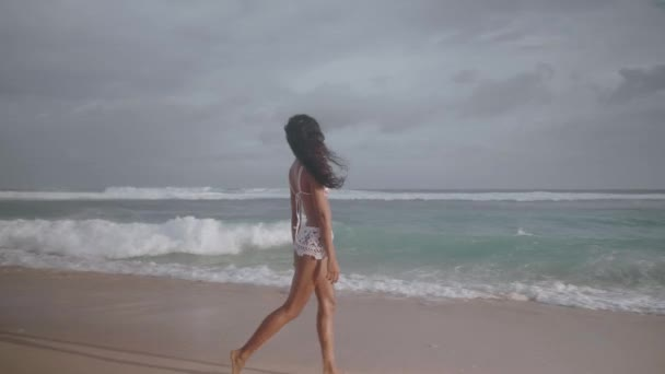 Beautiful happy girl relaxing at the sandy beach over ocean and cloudy sky background - video in slow motion