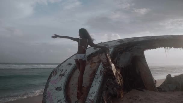 Beautiful girl posing on the shipwreck at the sandy beach during amazing sunset - video in slow motion