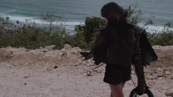 Beautifu happy woman motorcycle rider walking with helmet near amazing limestone cliffs over sea  background - video in slow motion