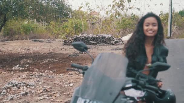 Portrét krásná žena motocyklu jezdec dělat zastávky na skútru nad krajinou pozadí - video v pomalém pohybu