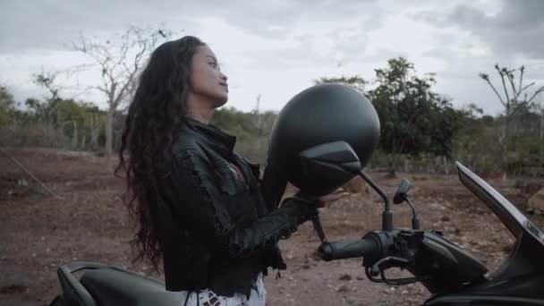 Portrét krásné ženy motocyklový závodník nasadil helmu nad krajinou pozadí s krávy - video v pomalém pohybu