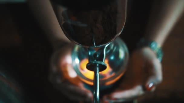 Female hands covering fire under vacuum with Luwak coffee. Amazing view of alternative coffee maker machine - video in slow motion