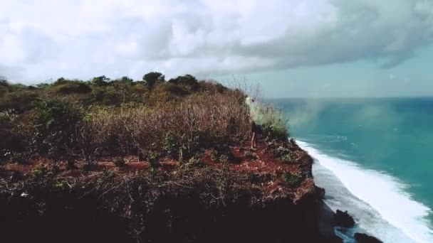 Aerial drone shot of pretty girl playing  with colored smoke on the cliff with amazing ocean and cloudy sky view - video in slow motion