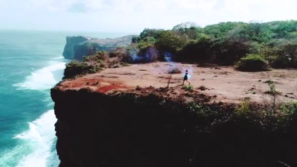 Aerial drone shot of pretty girl playing  with colored smoke on the cliff with amazing ocean and cloudy sky view
