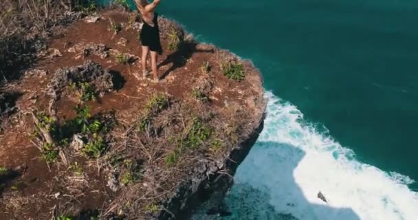 Aerial drone shot of pretty girl standing on the cliff with amazing ocean and cloudy sky view - video in slow motion